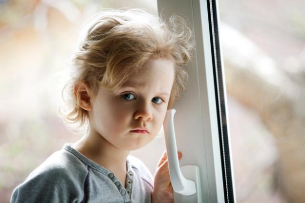 child by the window shutterstock_135572696