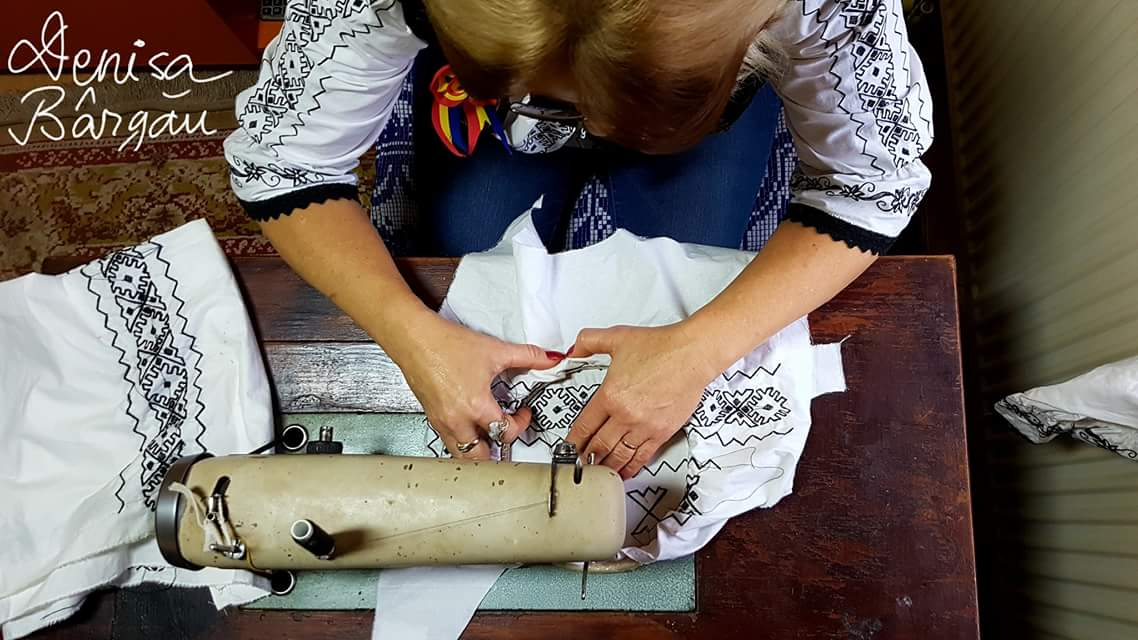 Mirela Groza din Luncoiu de Jos coase la mașină un costum popular cu motive tradiționale